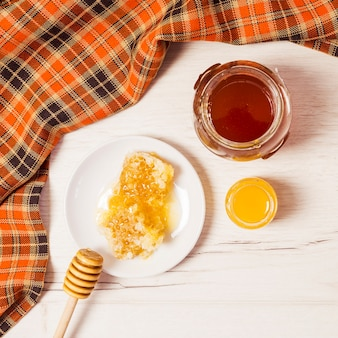 Jar of honey; honeycomb; honey dipper and table cloth over white desk