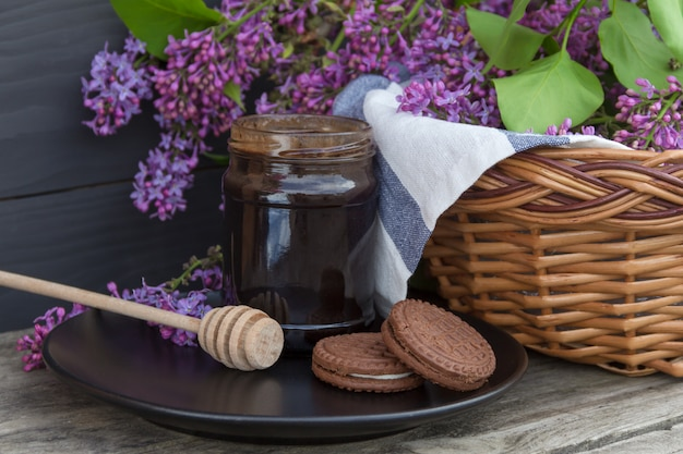 A jar of honey or jam with wicker basket with lilac on wooden table.
