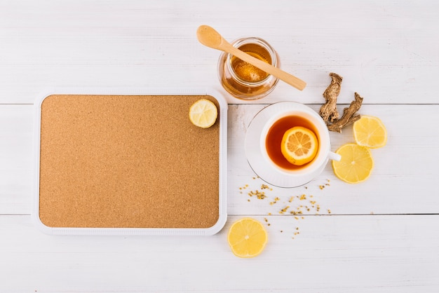 Jar of honey and lemon tea near ginger on wooden background