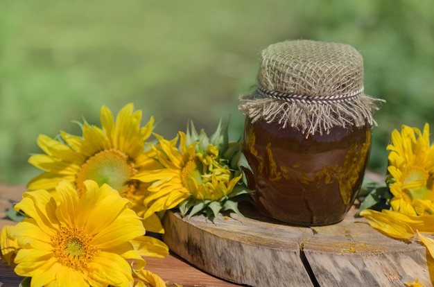 Jar of honey and sunflowers on wooden table over bokeh garden background