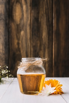 Jar of honey with beautiful flowers on wooden surface