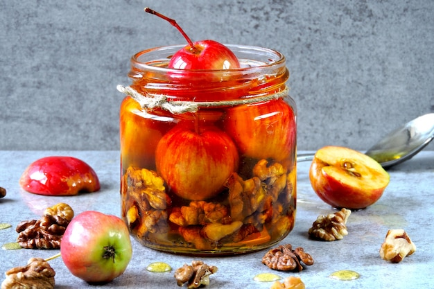 A jar of honey with small apples and nuts.