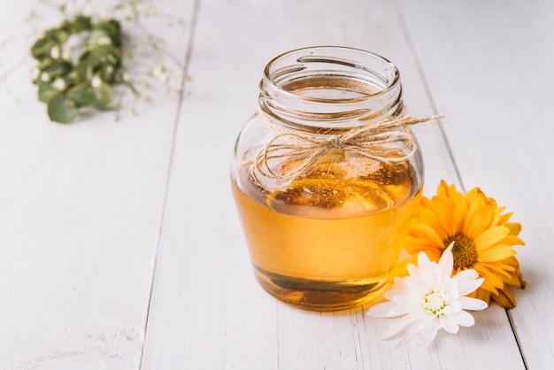 Jar of honey with white and yellow flower on wooden background
