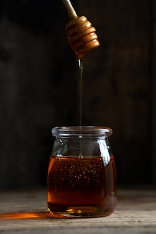Jar of honey on a wooden surface
