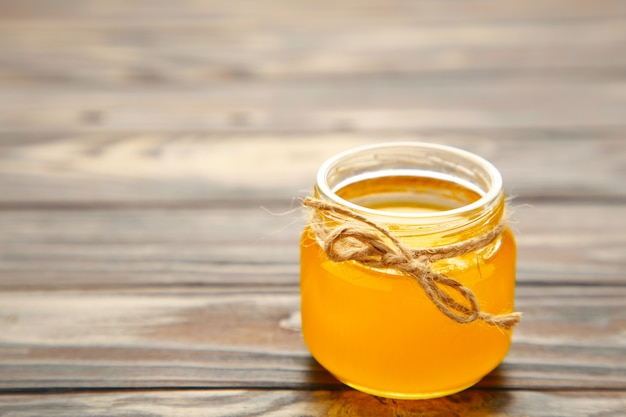 Jar of honey on wooden table. top view