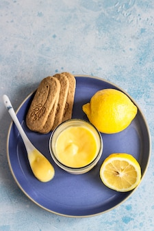 A jar of lemon curd or custard and cookies on a blue plate.