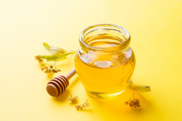 A jar of liquid honey from linden flowers and a stick with honey on yellow surface. copy space