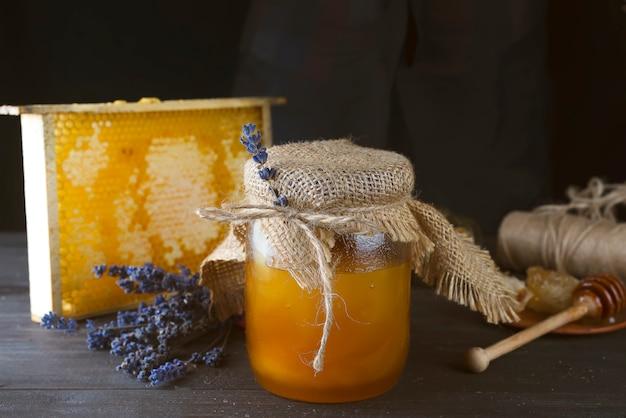 Jar of liquid honey with honeycomb