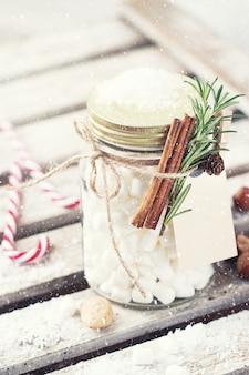 Jar of marshmallows with cinnamon and caramel sticks