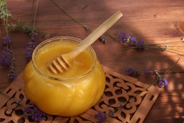 A jar of natural honey with a spindle spoon on a mat on the table next to lavender.