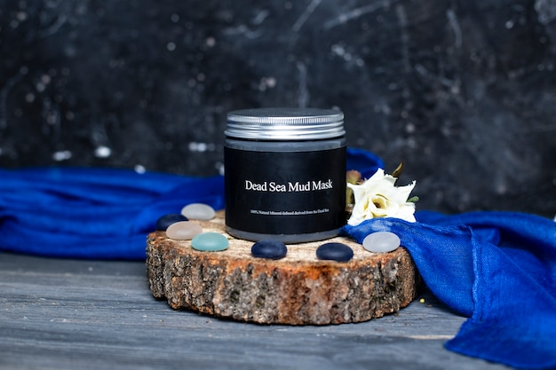 A jar of natural skin care dead sea mud mask with silver cap on wood