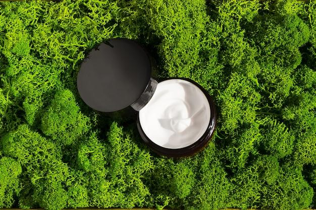 スキンケア化粧品スパとウェルネスセンターのフェイシャルトリートメントの顔と体のコンセプトのための光有機粘土マスククリームの朝の光線の緑の苔の背景に美容クリームの瓶