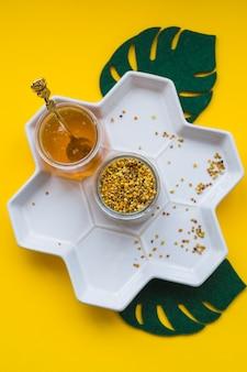 꿀벌 꽃가루와 노란색 배경 위에 흰색 쟁반에 꿀 항아리