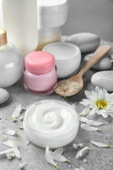 Баночка крема для тела и лепестки цветов на столе