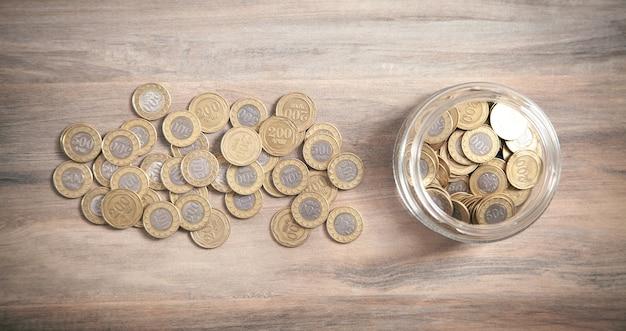 木製の背景にコインの瓶。