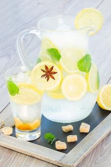 テーブルの上の背の高いガラスとクールなレモネードの瓶