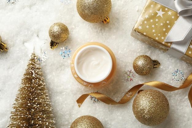 装飾的な雪の背景に化粧品クリームとクリスマスアクセサリーの瓶