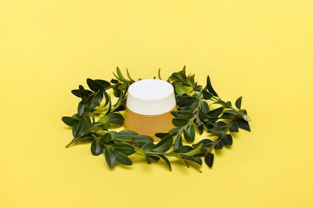 Баночка крема с декором из зеленых листьев на желтой поверхности