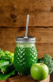 木製の壁に新鮮なデトックスグリーンのスムージーの瓶。