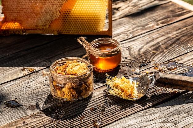 Баночка со свежим медом с различными инструментами для пчеловодства, деревянный дозатор и поднос с сотами из пчелиного улья в натюрморт на деревянном столе на открытом воздухе с местом для копирования