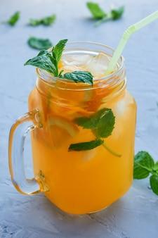 灰色の表面にオレンジスライス、氷、ミントの葉と新鮮なオレンジジュースの瓶