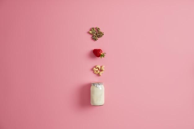 新鮮なヨーグルトとカボチャの種、熟した食欲をそそるイチゴ、カシューナッツなどの材料の瓶。自家製栄養素デザート。ダイエットとスーパーフードのコンセプト。朝食のためのおいしいアイデア。上から見る