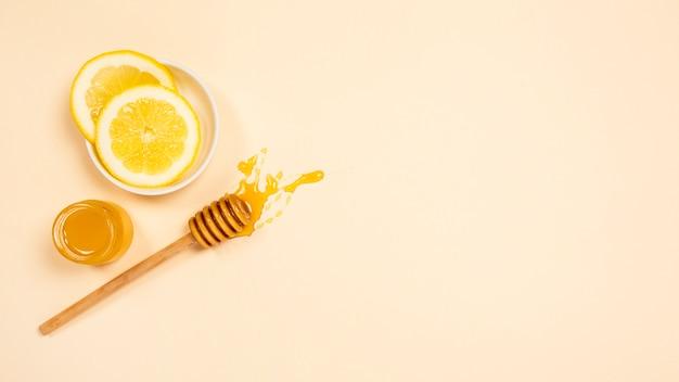 健康な蜂蜜の瓶と無地の表面に蜂蜜ディッパーのレモンスライス
