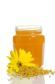 蜂蜜の瓶と花粉の山