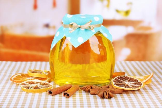 明るい表面に蜂蜜と乾燥レモンスライスの瓶
