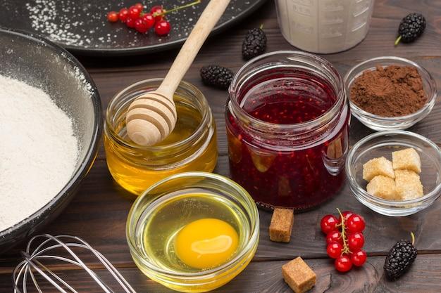 Баночка с медом и вареньем. разбитое яйцо в чашке. мука и ягоды. ингредиенты для запекания ягодного пирога. темная деревянная поверхность. вид сверху