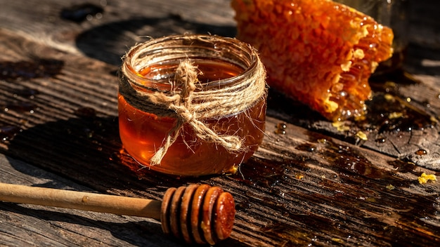 蜂蜜の瓶、蜂蜜の櫛と蜂蜜の棒は木製のテーブルに