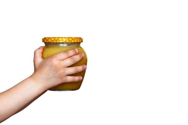 白い背景の上の子供の手の蜂蜜の瓶