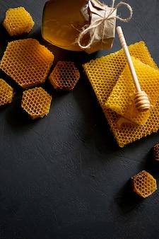 黒いテーブル、上面図に蜂の巣と蜂蜜の瓶。テキスト用のスペース