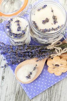 Банка лавандового сахара и свежих цветов лаванды на деревянном столе