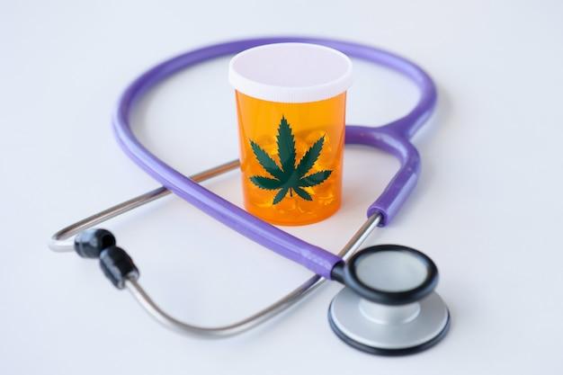 聴診器の近くに立っているマリファナの丸薬の瓶