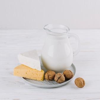 우유 병; 치즈와 호두 흰색 나무 테이블에