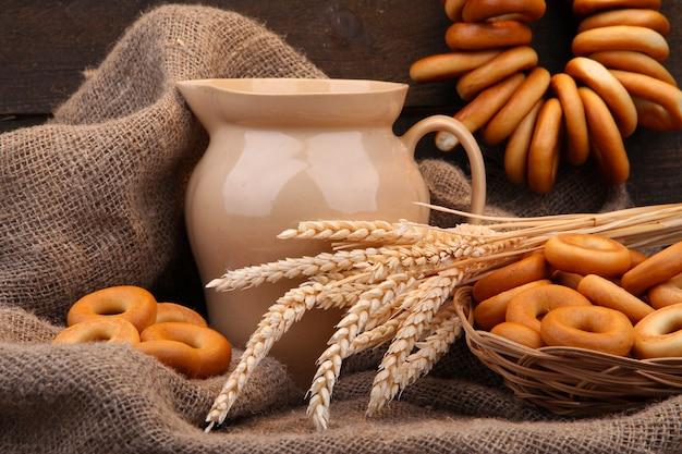 Банка молока, вкусные рогалики и колоски на деревянном столе