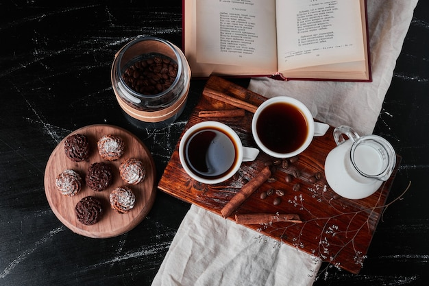 Банка молока с кофейными чашками и печеньем