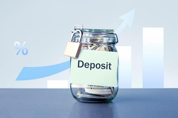 Банку с деньгами с надписью «депозит против диаграммы роста». прибыль от депозита в банке и дивиденды для концепции инвестиций в акции.