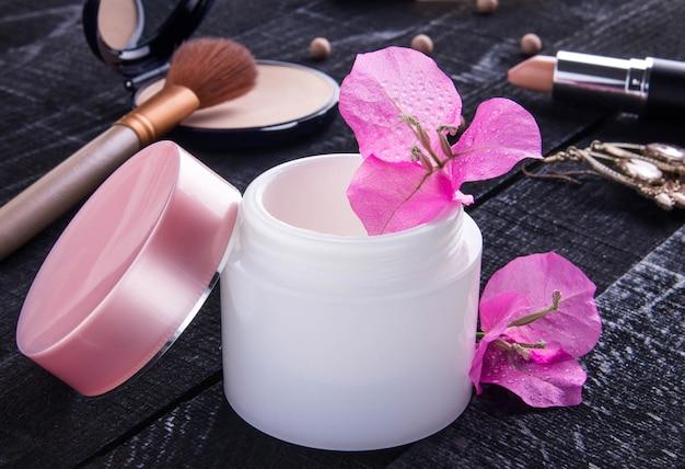 핑크 꽃과 자연 크림의 항아리입니다. 유기농 화장품 프리미엄 사진