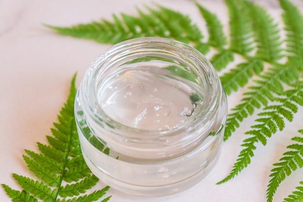 シダの葉の上の天然有機フェイスプランラーベースのジェルクリームの瓶。化粧品ブランドデザイン用のコピースペース