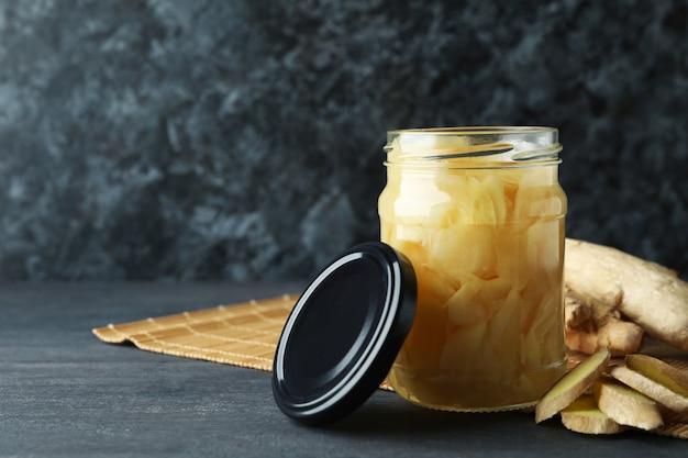 生姜のピクルスとダークウッドのテーブルの生姜の瓶