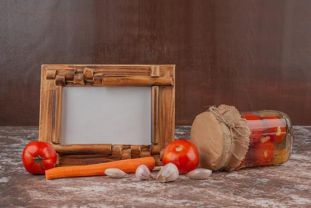 Баночка маринованных помидоров, свежих овощей и фоторамки на мраморном столе.