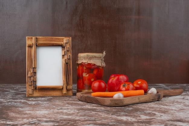 Банка маринованных помидоров, тарелка свежих овощей и рамка для фотографий на мраморном столе.