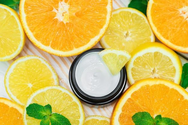 Баночка белого крема для тела цитрусовый крем на фоне апельсинов и лимонов. натуральный цитрусовый крем для лица для антивозрастного эффекта.