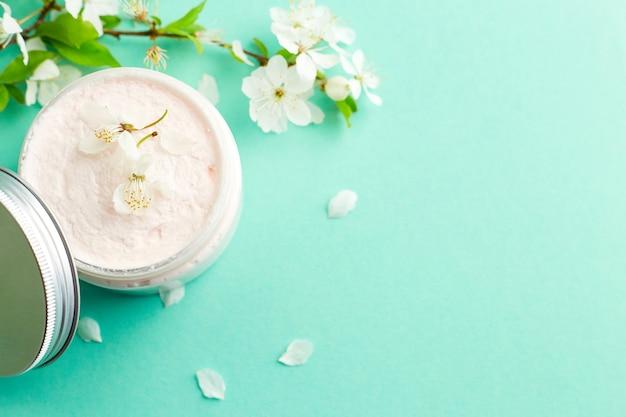 新鮮な春の桜の花と白いスキンケアクリームの瓶