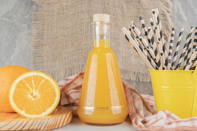 Barattolo di succo d'arancia con arance fresche sulla superficie in marmo