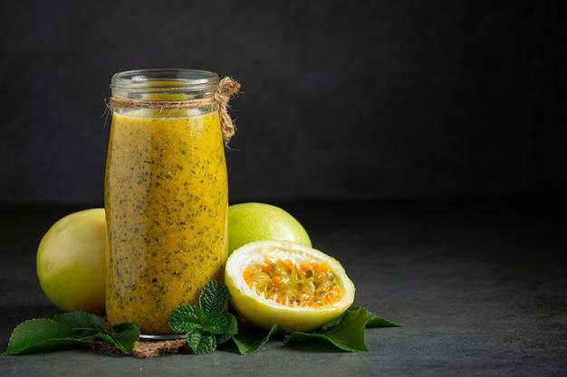 Un barattolo di succo di frutto della passione e frutto della passione fresco tagliato a metà sul pavimento scuro