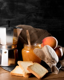 Jar of peach jam with bread and kettle