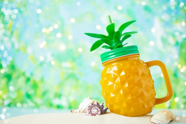 Jar of pineapple juice on the sand with shells on the summer sea background